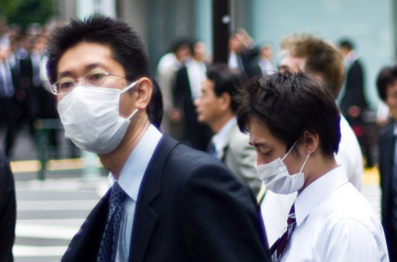 Businessmen protect themselves from an H1N1 outbreak on a Tokyo street